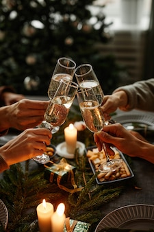 Vertical close up of four people enjoying christmas dinner together and toasting with champagne glas...