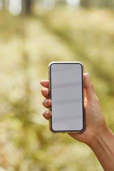 Вертикальный крупный план женской руки, держащей смартфон с пустым экраном в лесных путешествиях и навигации ...