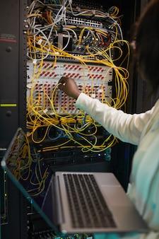 Вертикальный крупный план женского сетевого инженера, соединяющего кабели в серверном шкафу во время работы с суперкомпьютером в центре обработки данных, копировальное пространство