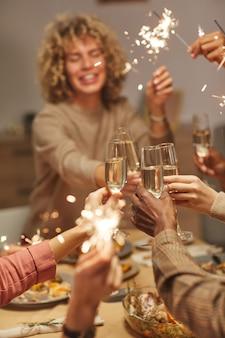 Вертикальный крупный план людей, подающих тосты с бокалами шампанского, наслаждаясь ужином с друзьями и семьей и держа в руках бенгальские огни