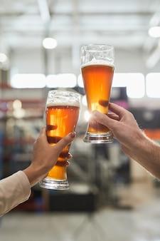 醸造所、コピースペースでの生産とろ過の品質を検査しながら、ビアグラスを持っている2人の労働者の垂直クローズアップ