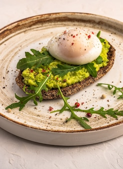 Vertical close up poached egg toast with avocado, salted salmon, arugula and rye bread on a ceramic plate, healthy food concept