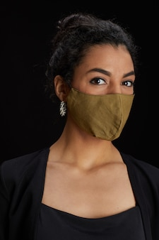 Vertical close up portrait of elegant middle-eastern woman wearing face mask while posing against black background at party