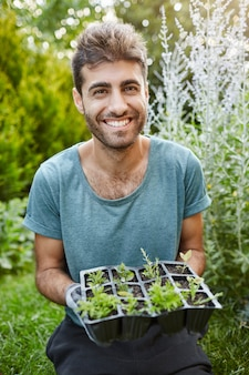 Vertical close up portrait of mature good-looking bearded gardener in blue t-shirt smiling in camera, holding pot with planted sprouts in hands.