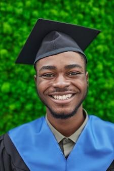 卒業式の帽子をかぶって、緑の植物の背景に立っている間カメラに笑みを浮かべて幸せなアフリカ系アメリカ人男性の垂直クローズアップの肖像画