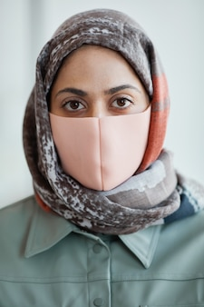 마스크를 쓰고 카메라를 바라보는 현대 중동 여성의 세로 클로즈업 초상화