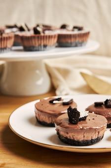 Primo piano verticale dei muffin cremosi della torta di formaggio del cioccolato sui piatti sotto le luci