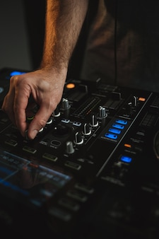 Vertical closeup of a dj working in a nightclub