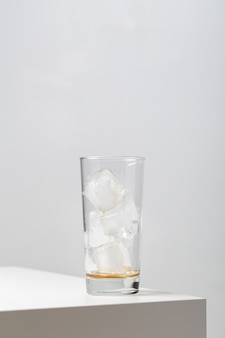 Vertical closeup of an empty glass with ice cubes in it on the table under the lights