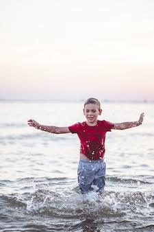 Ritratto verticale del fuoco del primo piano di un giovane ragazzo che sta nel mare