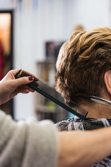 Primo piano verticale di un parrucchiere che taglia i capelli corti di una donna in un salone di bellezza