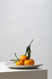 Vertical closeup of mandarines on a plate on the table under the lights on white
