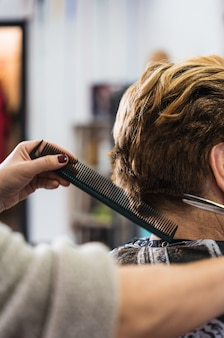 Вертикальный крупный план парикмахера, стригущего короткие волосы женщины в салоне красоты