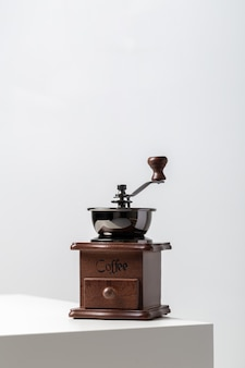 Вертикальный крупный план мини-винтажной кофемолки на столе под огнями