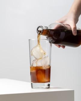 Вертикальный крупный план человека, разливающего чай в стакан с кубиками льда в нем на столе