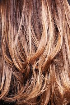 조명 아래에서 여자의 가벼운 물결 모양의 머리의 수직 근접 촬영