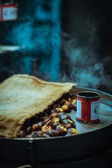 ライトの下で鍋に缶とローストナッツの垂直クローズアップ