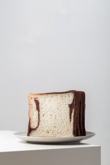ライトの下でテーブルの上のプレートにチョコレートと混合した白パンのスライスの垂直クローズアップ
