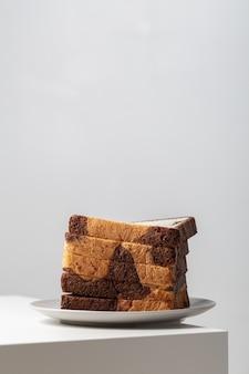 Вертикальный крупный план ломтиков белого хлеба, смешанных с шоколадом на тарелке на столе под огнями