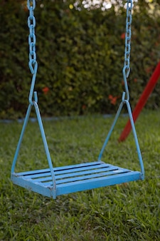 Vertical closeup of an old blue swing in a garden surrounded by greenery in mexico
