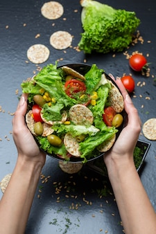 Vertical closeup of a person holding a bowl of salad with crackers and vegetables under the lights