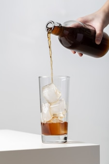 Vertical closeup of a person pouring tea in a glass with ice cubes in it on the table