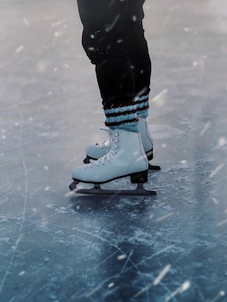 Vertical closeup of a person in white skates on the ice during the snowfall