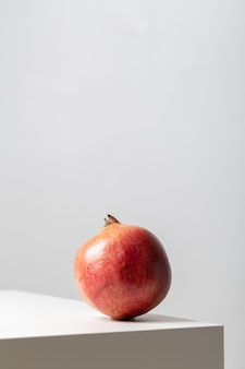 Vertical closeup of a pomegranate on the table under the lights on white