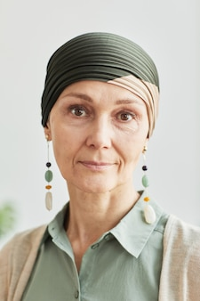 Vertical closeup portrait of mature woman wearing headscarf and looking at camera calmly