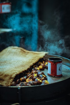 Vertical closeup of roasted nuts with a can on a pan under the lights