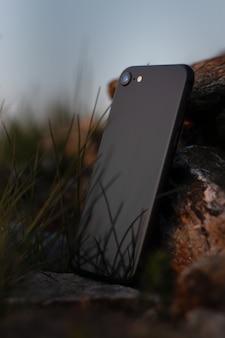 Colpo verticale del primo piano di uno smartphone nero appoggiato su una pietra