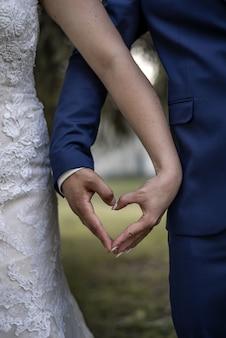 Colpo verticale del primo piano di una sposa e uno sposo che formano un cuore con le loro mani
