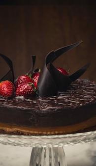 Colpo verticale del primo piano di una torta al cioccolato con fragole in cima