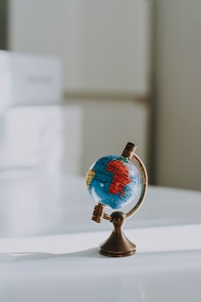 Vertical closeup shot of a decorative small globe on a white desk and blurred