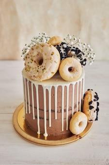 Chiusura verticale di una deliziosa torta di compleanno al cioccolato con ciambelle in cima e gocciolamento bianco