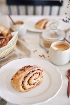 Vertical closeup shot of delicious nut snails with coffee cappuccino on the white wood table