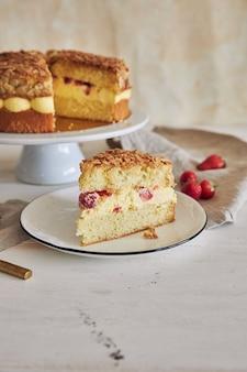 Colpo verticale del primo piano della deliziosa torta alla crema alla vaniglia con fragole all'interno su un tavolo bianco