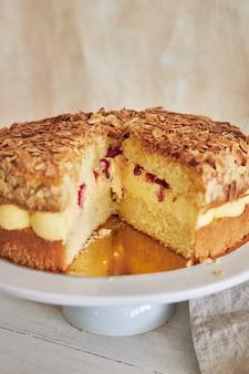 垂直的特写镜头射击了可口香草奶油蛋糕用在一张白色桌上的草莓