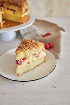 Primo piano verticale della deliziosa torta alla crema di vaniglia con fragole all'interno su un tavolo bianco