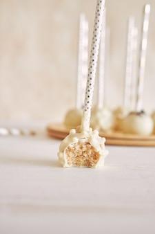 Colpo verticale del primo piano di una deliziosa torta bianca che si apre su un tavolo bianco