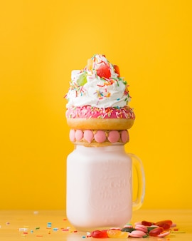 Vertical closeup shot of a dessert with a doughnut and whipped cream on a drinking jar