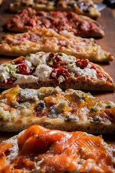 Colpo verticale del primo piano di diversi tipi di pizza sul tavolo