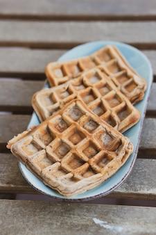 Colpo verticale del primo piano di deliziosi waffle appena sfornati serviti sul piatto bianco all'aria aperta
