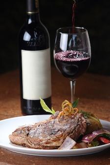 Colpo verticale del primo piano di una bistecca alla fiorentina appena grigliata e un bicchiere di vino in background