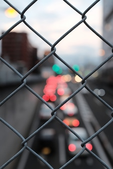 Vertical closeup shot of gray chain link fence on a blurry background of street