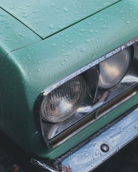 Vertical closeup shot of a green car headlamps