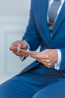 Colpo verticale del primo piano di uno sposo in un vestito alla moda blu