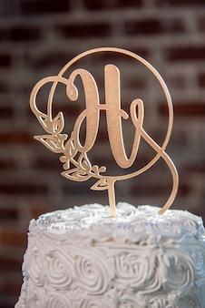 Colpo verticale del primo piano di una guarnizione a forma di h su una bella torta nuziale bianca