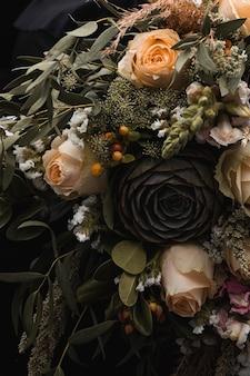 Colpo verticale del primo piano di un lussuoso bouquet di rose arancioni e marroni su fondo nero