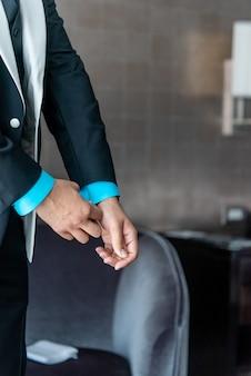 Colpo verticale del primo piano di un maschio che fissa la manica blu del costume